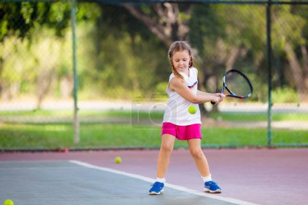 Photo for Child playing tennis on indoor court. Little girl with tennis racket and ball in sport club. Active exercise for kids. Summer activities for children. Training for young kid. Child learning to play. - Royalty Free Image