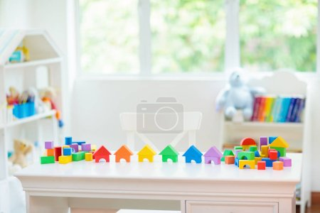 Photo for Kids bedroom with white desk and educational toy blocks. Colorful block toys for young children. Nursery room or day care. Kindergarten or preschool class for boy or girl. - Royalty Free Image