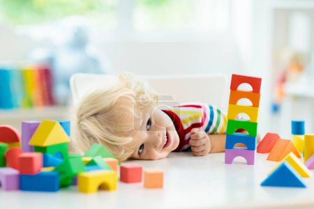 Photo for Kid playing with colorful toy blocks. Little boy building tower of block toys. Educational and creative toys and games for young children. Baby in white bedroom with rainbow bricks. Child at home. - Royalty Free Image