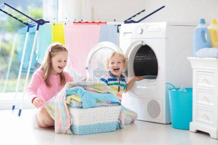 Niños en la sala de lavandería con lavadora o secadora. Los niños ayudan con las tareas familiares. Dispositivos domésticos modernos y detergente de lavado en casa soleada blanca. Limpiar la ropa lavada en el estante .