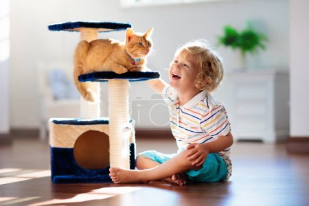 Photo for Child playing with cat at home. Kids and pets. Little boy feeding and petting cute ginger color cat. Cats tree and scratcher in living room interior. Children play and feed kitten. Home animals. - Royalty Free Image