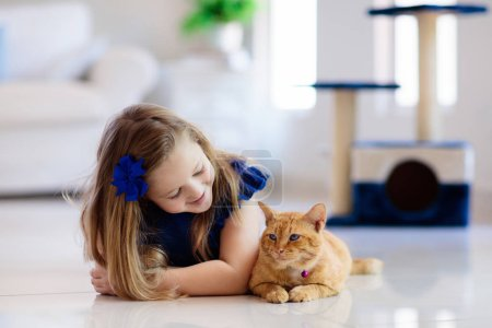 Photo for Child playing with cat at home. Kids and pets. Little girl feeding and petting cute ginger color cat. Cats tree and scratcher in living room interior. Children play and feed kitten. Home animals. - Royalty Free Image