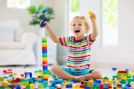 Photo for Child playing with colorful toy blocks. Little boy building tower at home or day care. Educational toys for young children. Construction block for baby or toddler kid. Mess in kindergarten play room. - Royalty Free Image