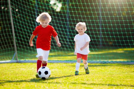 Photo for Kids play football on outdoor field. Children score a goal at soccer game. Little boy kicking ball. Running child in team jersey and cleats. School football club. Sports training for young player. - Royalty Free Image