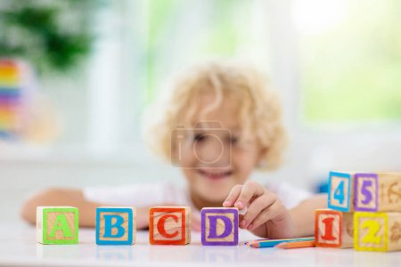 Photo for Child learning letters and numbers. Kid with colorful wooden abc blocks. Little boy spelling words with educational block toys. Kids doing school homework at white desk. Bedroom for preschool children - Royalty Free Image