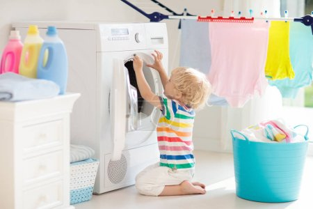 Photo for Child in laundry room with washing machine or tumble dryer. Kid helping with family chores. Modern household devices and washing detergent in white sunny home. Clean washed clothes on drying rack. - Royalty Free Image