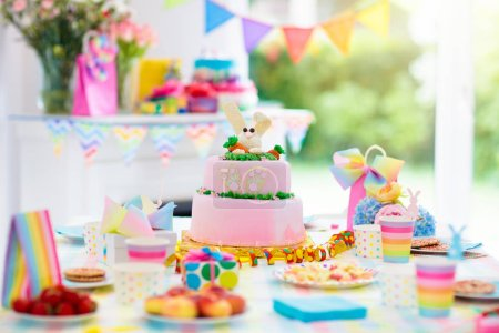 Photo for Kids birthday party decoration and cake. Decorated table for child birthday celebration. Rainbow bunny cake for little girl. Room with festive balloons, colorful banners in baby pastel color. - Royalty Free Image