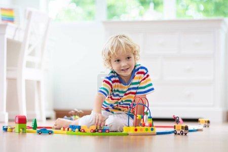 Photo pour Les enfants jouent avec le chemin de fer en bois. Enfant avec le train de jouet. Jouets éducatifs pour les jeunes enfants. Petit garçon construisant des voies ferrées sur le plancher blanc à la maison ou à la maternelle. Gosse mignon jouant des voitures et du moteur. - image libre de droit