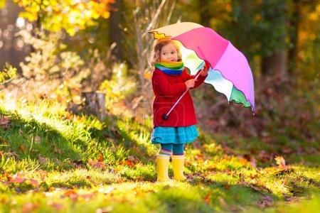 Photo pour Il joue sous la pluie. Les enfants avec parapluie et bottes de pluie jouent à l'extérieur sous de fortes pluies automnales. Petite fille sautant dans une flaque boueuse. Enfants amusants par temps pluvieux d'automne. Enfant qui court dans la tempête . - image libre de droit