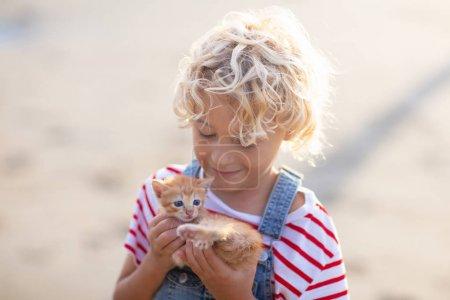 Petite fille tenant un bébé chat. Enfants et animaux domestiques