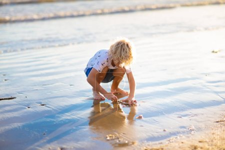 Photo for Kids playing on tropical beach. Children play at sea on summer family vacation. Sand and water toys, sun protection for young child. Little boy digging sand, building castle at ocean shore. - Royalty Free Image
