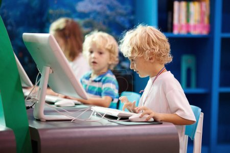 Photo for Kids with computer. Children learning and studying information and communications technology using personal computers in school class or library. Student at pc. Modern education device for child. - Royalty Free Image