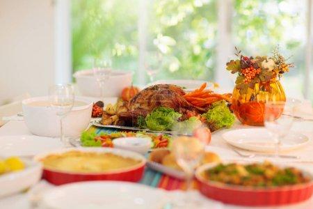 Photo pour Le dîner de Thanksgiving. Dinde rôtie avec farce et légumes pour la fête de famille. Table de vacances d'automne. Délicieux repas et boissons faits maison à la fête. Décoration de citrouille et de feuilles d'automne. - image libre de droit