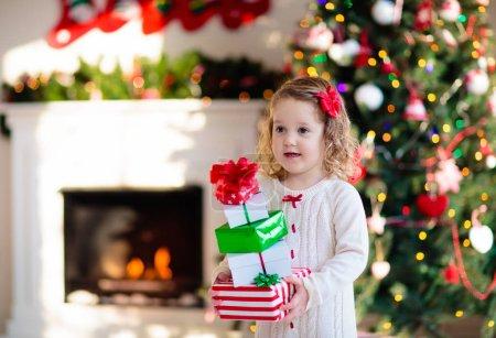 Photo pour Famille le matin de Noël à la cheminée. Les enfants ouvrent des cadeaux de Noël. Enfants sous l'arbre de Noël avec des boîtes-cadeaux. Salon décoré avec cheminée traditionnelle. Cozy chaude journée d'hiver à la maison. - image libre de droit