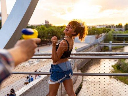 Lachen fröhlich mit Wasserpistolen planschen Menschen spielen und haben Spaß an einem heißen Sommertag.