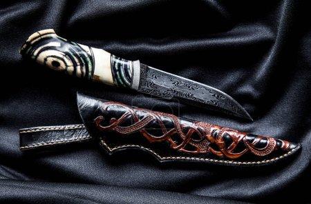 Photo pour Couteau Hunter avec manche en bois sur un fond sombre a - image libre de droit