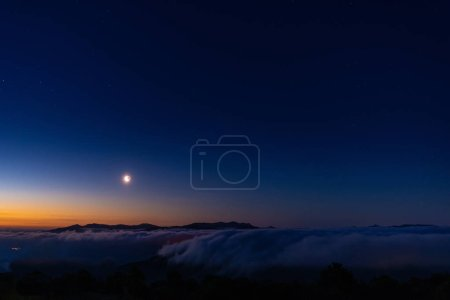 Early morning on mountains with moon over a  sea