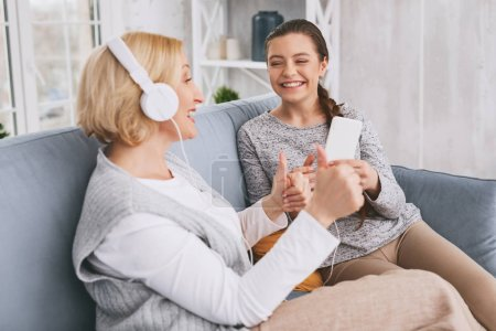 Pleased mature woman listening to music