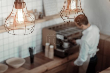 Competent barista making coffee for client
