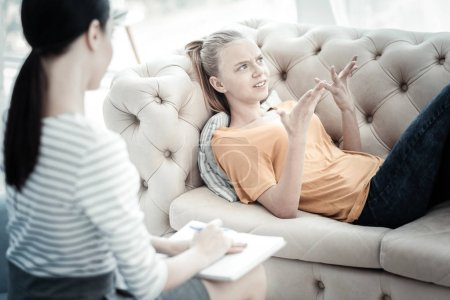 Photo for Therapy in progress. Miserable emotional teen girl lying on sofa while consulting with female psychologist who sitting with notebook - Royalty Free Image