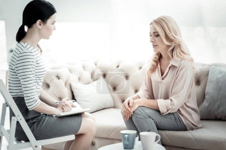 Focused female psychologist supporting woman