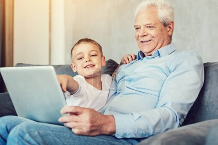 Photo for Check it. Cheerful happy little boy pointing at the screen of a big laptop while sitting on a sofa with his pleasant senior grandfather - Royalty Free Image