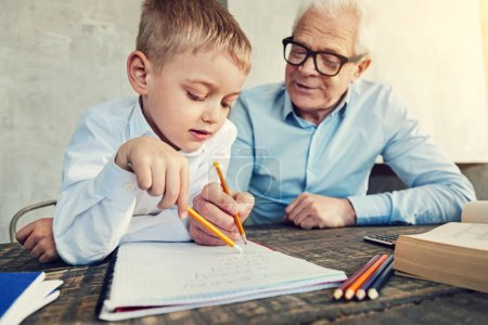 Attentive pupil doing homework with his grandfather