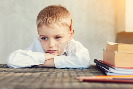 Sad little boy sitting at the table