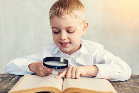 Photo pour Ferme là. Joyeux petit garçon heureux lisant un livre intéressant à l'aide d'une loupe - image libre de droit