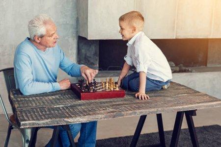 Kind smiling grandpa looking at his smart grandson