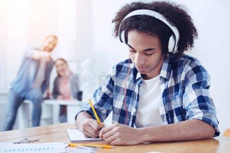 Photo pour Amoureux de musique. Jeune homme confiant inclinant la tête et regardant vers le bas tout en prenant des notes - image libre de droit