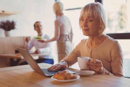 Pleasant woman drinking coffee and surfing the Internet