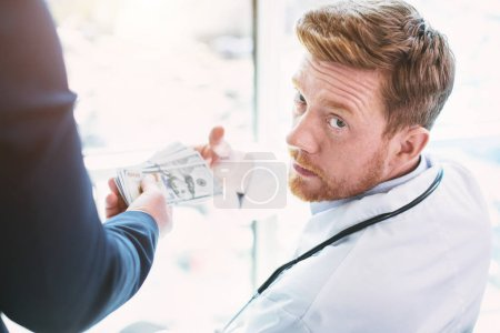 Immoral doctor taking a bribe for operation