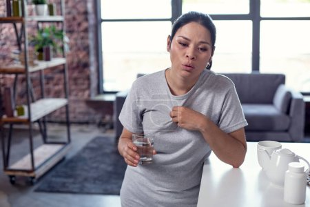 Exhausted gloomy woman getting symptoms of flu
