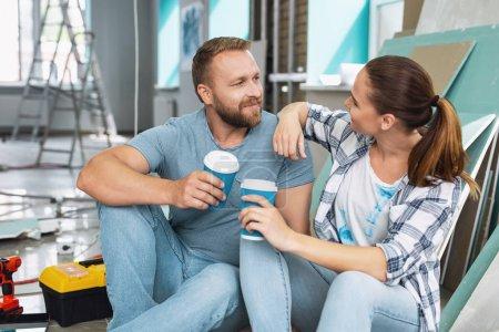 Photo pour Ma chère. Beau contenu homme prenant un café avec sa petite amie et la regardant - image libre de droit