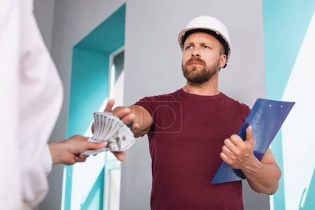 Indignant builder refusing to take a bribe