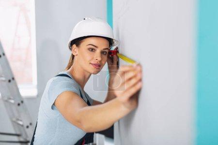 Grave mujer builder con una cinta métrica