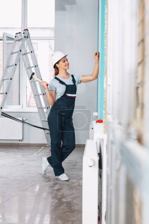 Content female builder holding a hammer