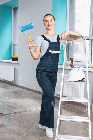 Delighted female builder holding a roller