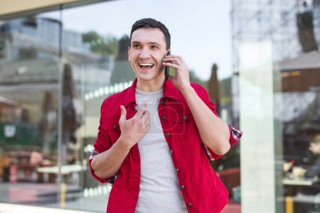 Photo for Red jacket. Stylish man wearing red denim jacket speaking on the phone with his loving girlfriend - Royalty Free Image