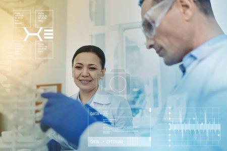Photo pour Étudier les chaînes. Biologiste professionnelle intelligente souriant alors qu'elle était assise dans un laboratoire à côté de son collègue expérimenté - image libre de droit