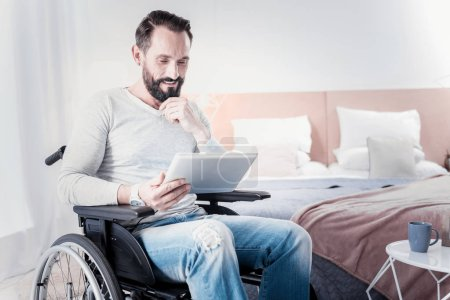 Photo for My leisure. Content handicapped man sitting in a wheelchair and holding a tablet - Royalty Free Image