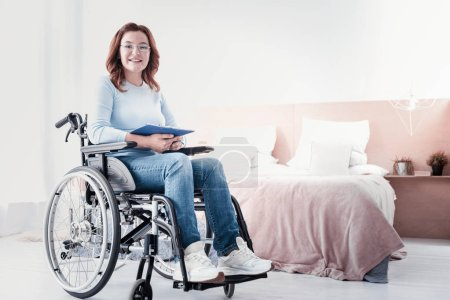 Photo for Happy freelancer. Cheerful disabled freelancer sitting in the wheelchair and working - Royalty Free Image