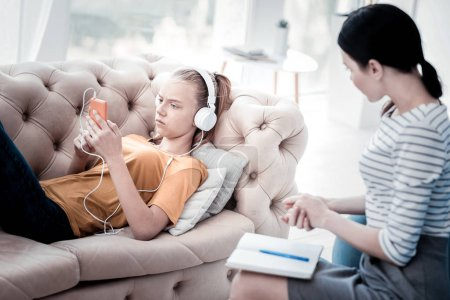 Photo for Trying psychological exercise. Upset girl lying on the sofa and listening to music while skilled psychologist holding notes on knees and observing her behavior - Royalty Free Image