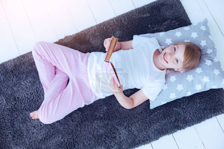 Relaxed girl smiling into camera while reading