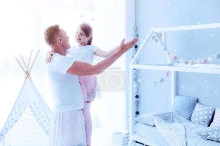Loving father dancing with little daughter at home