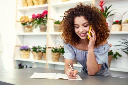 Positive joyful woman taking notes