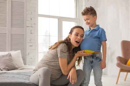 Photo pour Amusant de fils. Femme belle enceinte amusant sa petite boule de fils tout en mettant le jaune sous son Polo bleu - image libre de droit