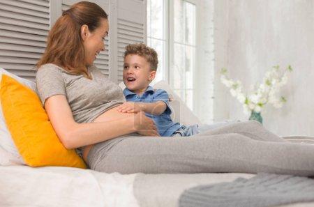 Photo pour Rire avec maman. Curly haired curieux petit garçon un large sourire tout en riant aux éclats avec sa mère enceinte - image libre de droit