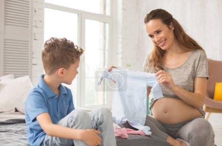 Photo pour Femme rayonnante. Rayonnant d'une femme enceinte se sentir tout simplement incroyable tout en montrant des mignons petits vêtements pour bébé à venir à son fils - image libre de droit
